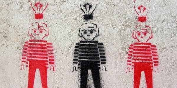 Sprayed stencil of three boys with light bulbs above their heads