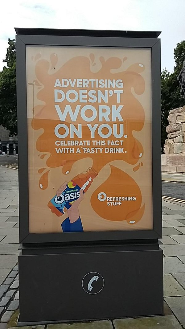 A photo of a bus stop billboard advertising Oasis drink