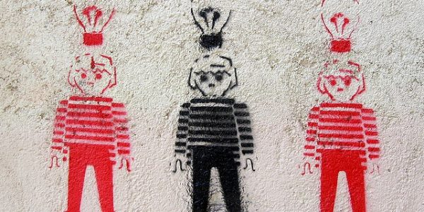Sprayed stencil of three boys with light bulbs above their heads