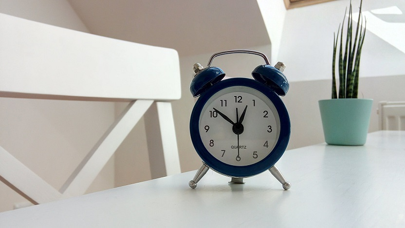 Photo of a blue alarm clock on a white table